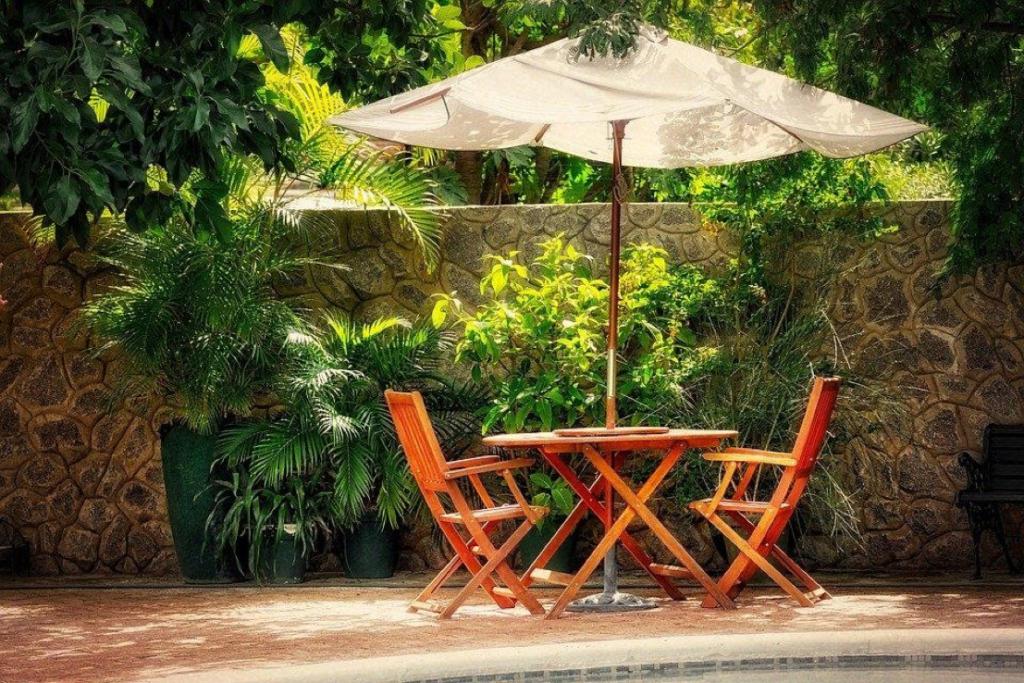 Salon de jardin en bois sous l'ombre des arbres et d'un parasol